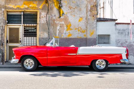 coche clásico convertible rojo al lado de un edificio en mal estado en la Habana Vieja Foto de archivo