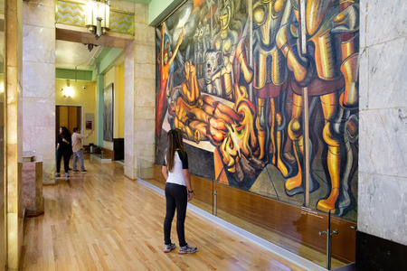 Visitor admiring a famous mural painting by David Alfaro Siqueiros at the museum of Palacio de Bellas Artes in Mexico City