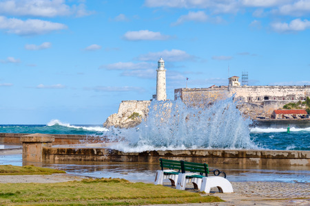 The fortress and lighthouse of El Morro in Havana with waves crashing on the Malecon seawall Editorial