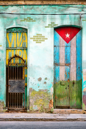 Antigua casa destartalada en La Habana con una bandera cubana pintada en su puerta y las palabras Viva Cuba Foto de archivo - 71347563