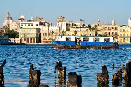 wharf: HAVANA,CUBA - FEBRUARY 7,2017 : An old motorboat carries passengers across the bay of Havana with colorful buildings on the background Editorial