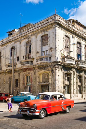 HAVANA,CUBA - FEBRUARY 3, 2016 : A vintage american car next to an crumbling old building in Havana Editorial