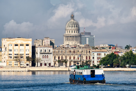 capitolio: Old Havana seaside buildings with a view of the Capitol and an old passenger motorboat crossing the bay