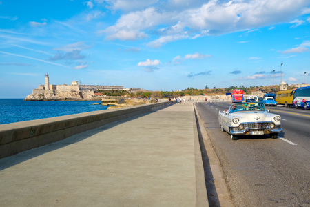 A classic vintage car rides along the Malecon avenue in Havana with El Morro castle on the background Editorial