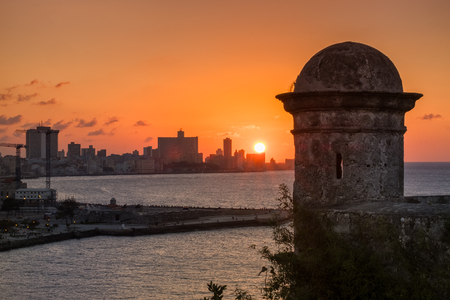 sunset city: The city of Havana at sunset with an old tower from a historic fortress on the foreground