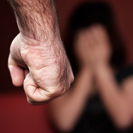 Domestic or gender violence - Aggressive man with a clenched fist threatens to hit a scared woman photo