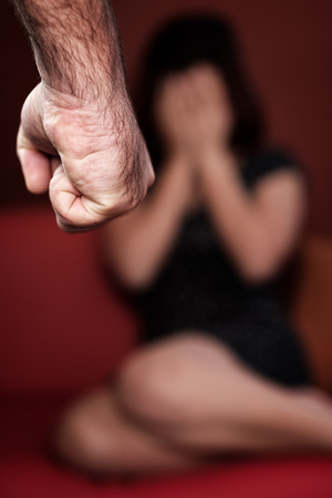 threatens: Domestic or gender violence - Aggressive man with a clenched fist threatens to hit a scared woman