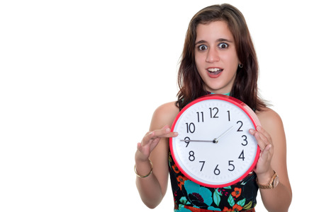 Beautiful teenage girl with a surprised expression showing the time on a big clock - Useful to illustrate lateness or the passing of time photo