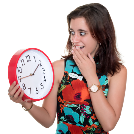 Beautiful teenage girl with a surprised expression checking the time on a big clock - Useful to illustrate lateness or the passing of time photo