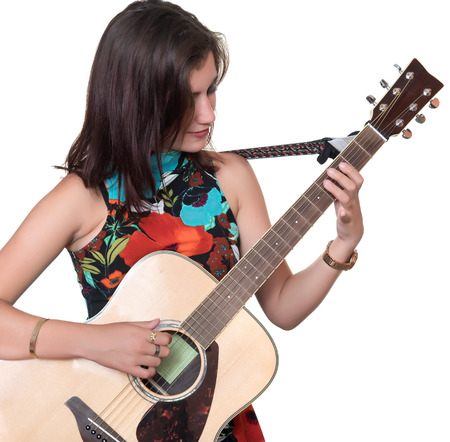 Beautiful teenage girl playing an acoustic guitar - Isolated on a white background photo