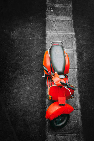 Red vintage italian scooter on a black and white background