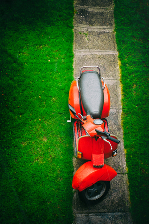 Top view of a red vintage italian scooter on a country road