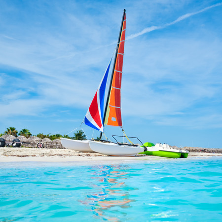 The beautiful beach of Varadero in Cuba with a colorful sailboat and turquoise water