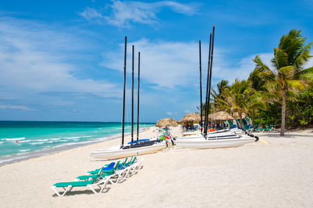 Beautiful summer day at Varadero beach in Cuba with sailboats and thatched umbrellas