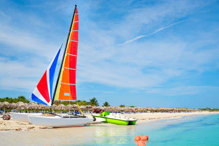 The beautiful Varadero beach in Cuba with a colorful sailboat and turquoise waves