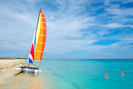 Summer day at Varadero beach in Cuba with a colorful sailboat