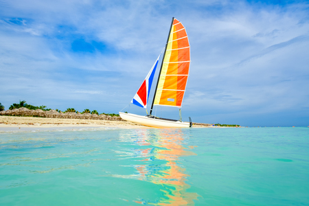 The tropical beach of Varadero on the island of Cuba with a colorful sailboat