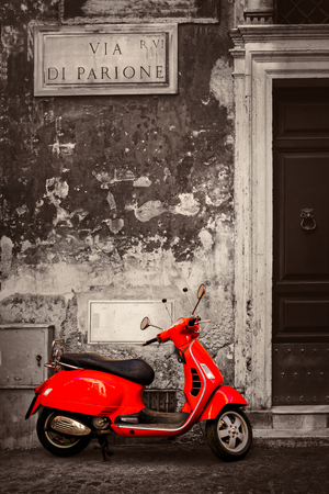 Black and white scene with a red scooter on a cobblestone covered narrow street in central Rome Stock Photo