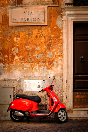 Typical scene with a red scooter on a cobblestone covered narrow street in central Rome