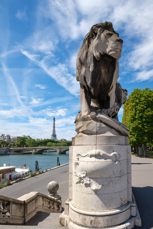 Statue of a lion at the bridge of Alexander III in Paris with the Eiffel Tower on the background Stock fotó