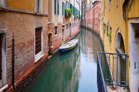 typical: Small boat on a narrow canal surrounded by old weathered buildings in Venice, Italy