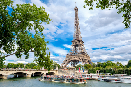 The Eiffel Tower and cruise boats on the river Seine on a summer day in Paris Redakční