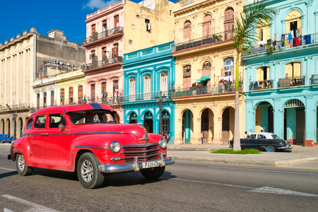 Urban scene with colorful buildings and old car in Havana