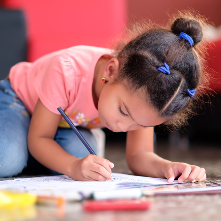 Cute multiracial small girl drawing on a coloring book while lying on the floor Stock Photo