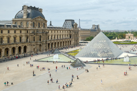 The famous Louvre Museum in Paris with the Eiffel Tower on the background