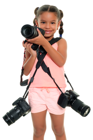 Cute multiracial small girl carrying three professional cameras - Isolated on a white background Banque d'images