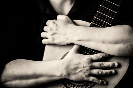 Hands hugging an acoustic guitar - Monochromatic on a black background