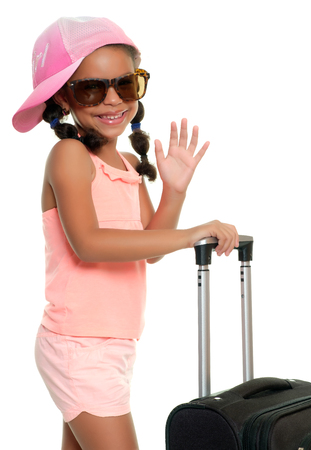 Multiracial small girl with sunglasses carrying a travel suitcase and waving goodbye - Isolated on a white background