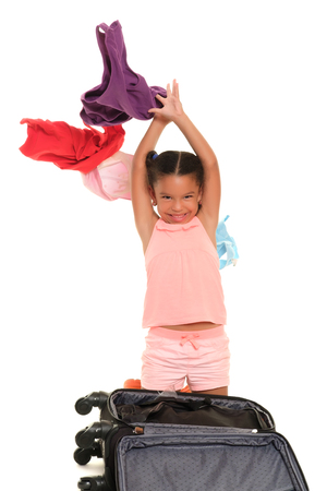 Multiracial small girl throwing clothes from a suitcase into the air - Isolated on a white background