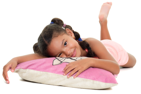 Cute multiracial small girl smiling laying on a cushion on the floor  - Isolated on a white background