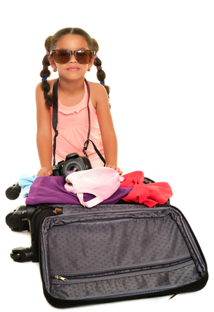 Multiracial small girl with sunglasses and a camera opening a travel suitcase - Isolated on a white background Stock Photo