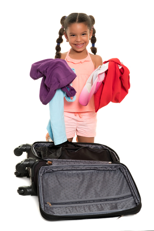 Cute african american girl taking out clothes from a travel suitcase - Isolated on white