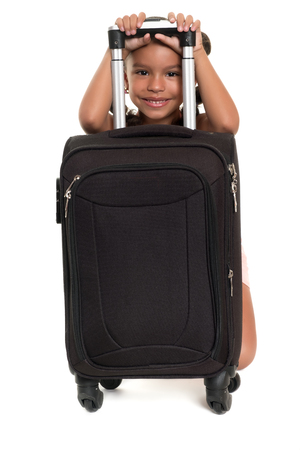 Cute african american girl hiding behind a travel suitcase - Isolated on white Stock Photo