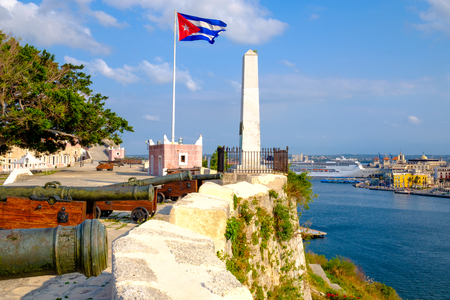 Cannons on an old colonial fortress with a cuban flag and a view of the bay of Havana