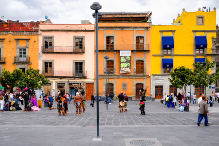 Colorful houses, people and street artists dressed as Aztecs in the historical center of Mexico City