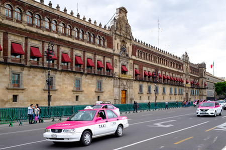 Typical pink taxis next to the National Palace in the historical center of Mexico City Редакционное