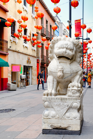 Stone lion and red paper lanterns at Chinatown in Mexico City Foto de archivo - 106400502