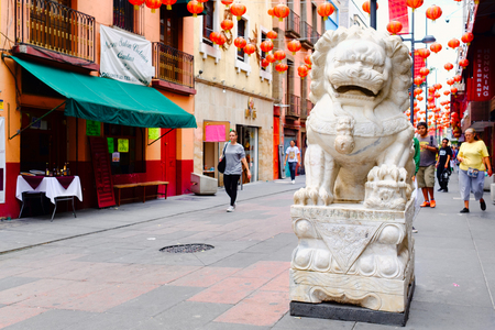 Stone lion and red paper lanterns at Chinatown in Mexico City