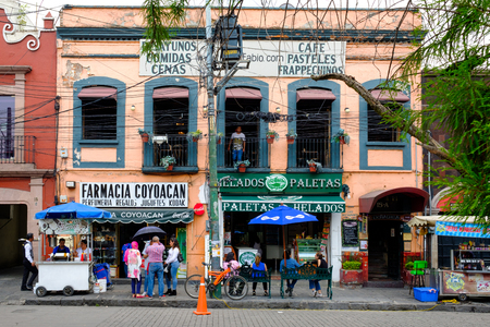 Local businesses at a colorful colonial building in Coyoacan, a historic neighborhhod in Mexico City Редакционное