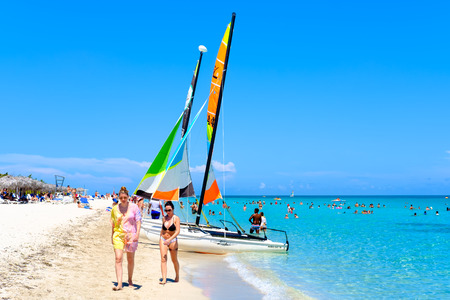 The famous Varadero beach in Cuba in a beautiful summer day with people and colorful sailboats Фото со стока