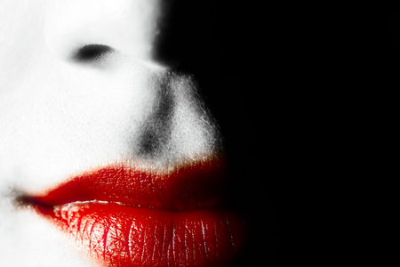 Red lips of a young woman on a black background Фото со стока