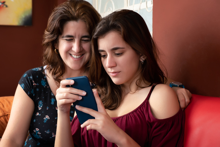 Hispanic teenage girl and her mother looking at a smartphone at home
