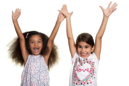Hispanic and african-american small girls laughing and raising their arms - Isolated on white Фото со стока