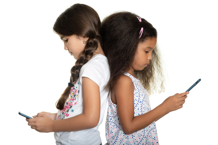 Two small girls staring at their smartphones - Isolated on white