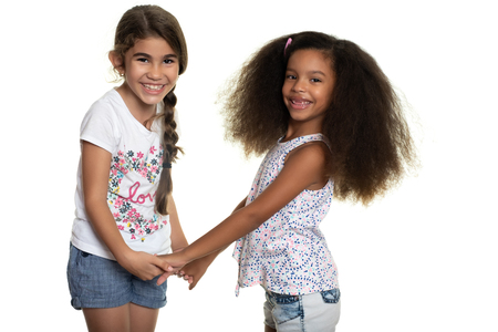Cute hispanic and african-american small girls holding hands  - Isolated on white