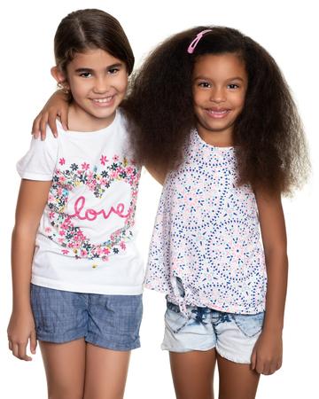 Petites filles hispaniques et afro-américaines mignonnes étreignant - d'isolement sur le blanc